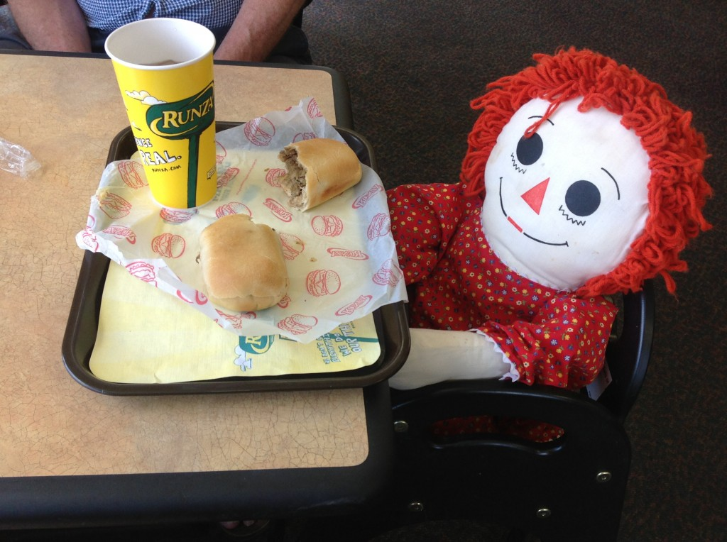 Ann eating a runza at a drive-in in Grand Island. One lady stopped and asked: Is the doll going to eat that all by herself? Ann let it go. A runza, if you haven't had one, is a yeast dough bread pocket with a filling of beef, pork, cabbage or sauerkraut, and onions. Originating in Russia in the 1800s, it was brought to the United States by the Russian-Germans in the early 1900s. Runza restaurants are as common in Nebraska as McDonalds or Burger Kings.
